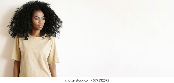 People and lifestyle. Studio shot of gorgeous African girl with Afro hairstyle wearing oversize t-shirt standing isolated at white wall and looking away with serious thoughtful expression on her face