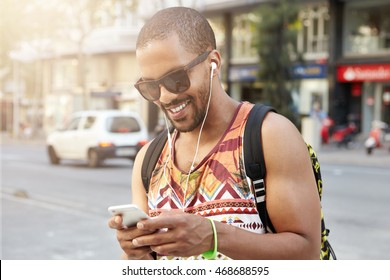 People, lifestyle and technology. Black college student having fun and relaxing after hard day at university, walking down street, listening to his favorite tracks and texting friends using cell phone