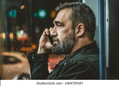 People, lifestyle, travel and public transport. Attractive man talking on the phone in public bus.
