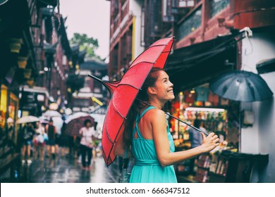 People lifestyle umbrella travel Asian woman shopping in chinatown market street. Rainy day girl tourist under red oriental umbrella in back alleys in Shanghai, China.