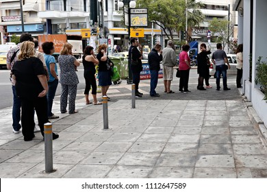 People line up outside a Piraeus Bank branch to use ATM machine, in Athens, Greece on Jun. 27, 2015