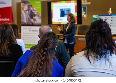 People listen to lady talk at conference. A view from behind an audience as a business woman speaks in an office setting. Attendees look on as speaker presents at a training event.