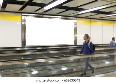 People looking Blank billboard in the city building, shot in subway station. Useful for your advertising.Selective Focus.