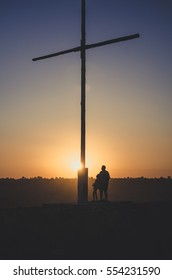People looking up at cross with sunset from behind