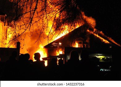 People looking an old Wooden house burning in the fire