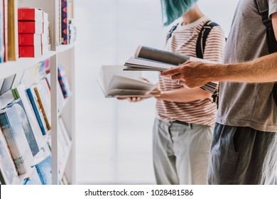 People looking through books at a library or a book store.