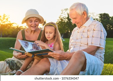 People looking through photo album. Caucasian girl with grandparents outdoors. Pages of the past.