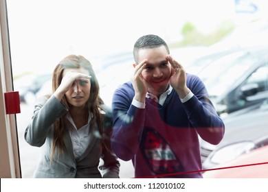 People looking through a shopwindow of a dealership