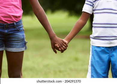 People in love with african little girl and boy holding hands in park. Cropped view
