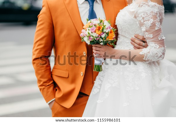 People, love, relationships and wedding ceremony concept. Unrecognizable groom and bride in festive clothes, stand closely and embrace, celebrate creation of their family and marriage, pose outdoor