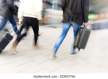 People with luggage in blurred motion to catch flight, train or ship.