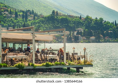 people lunch in an elegant floating restaurant on the lake Garda waters in Malcesine, Italy, 22 Apr 2019