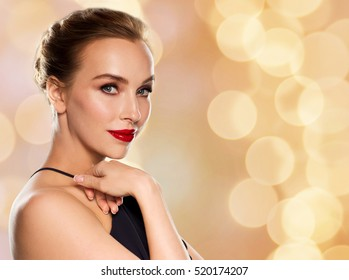 people, luxury and fashion concept - beautiful woman in black with red lips over holidays lights background