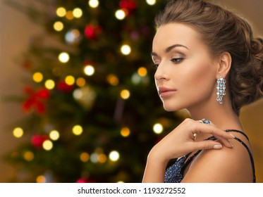 people, luxury, jewelry and fashion concept - close up of beautiful woman in black wearing diamond earring and ring over christmas tree lights background