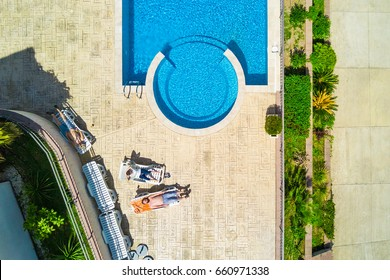 People lying on the sun loungers near the pool, top view