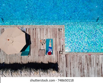 People lying on the sun loungers near the pool, top view in Asia