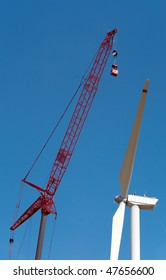 People make repairs wind turbines with the help of a crane