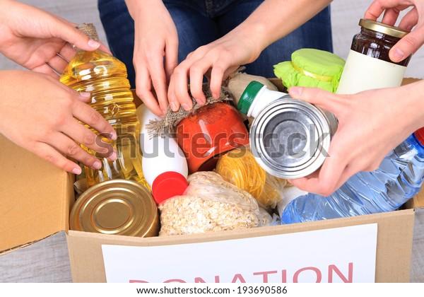Les gens fabriquent des denrées alimentaires à partir d'un coffret de don sur fond gris