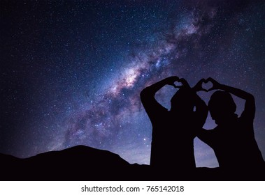 People makes heart symbol by hand with Milky Way and night sky on background.