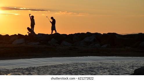 people making selfie by sunrise at sea