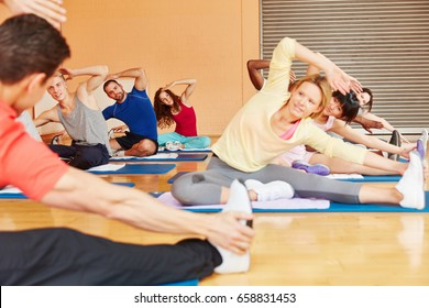People making stretching exercise in pilates class