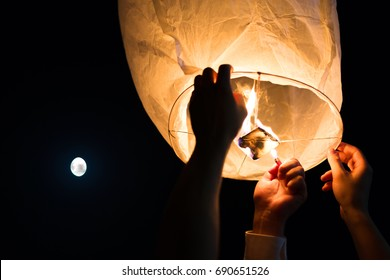 People making a wish and launching flying lantern to the sky at wedding party