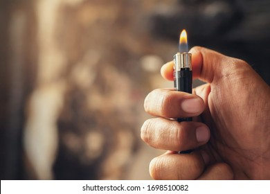 people man hand holding burning gas lighters arson conflagration damage background. Portable device used to create a flame. Safety and Set fire to insurance concept.  - Shutterstock ID 1698510082