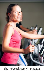 People - man and woman - exercising in a gym on an elliptical trainer for more fitness