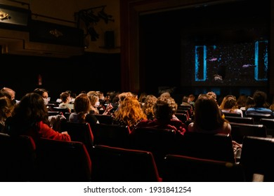 people with a mask watching a show in a theater maintaining sanitary measures