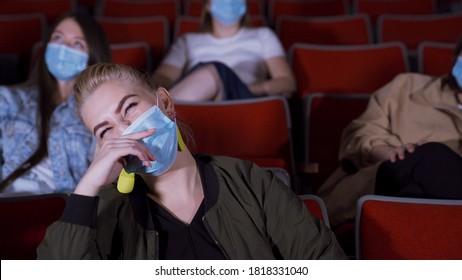 Les gens en masques regardent un film drôle. Médias. Des gens en masques médicaux s'assoient dans un cinéma et rient en regardant un film. Ouverture de cinémas pendant une pandémie de coronavirus