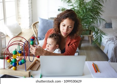 People, maternity, childcare, job and career concept. Portrait of university student girl of mixed race appearance working on research project on laptop pc and playing with her little son at desk