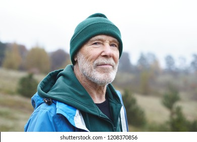 People, maturity age, retirement, nature, recreation and adventure concept. Portrait of handsome smiling senior male pensioner with thick gray beard, wrinkles and blue eyes walking outdoors