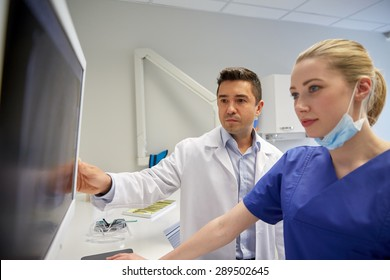 people, medicine, stomatology, technology and health care concept - dentists looking to x-ray scan on monitor at dental clinic