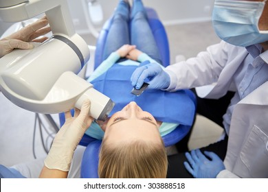 people, medicine, stomatology, technology and health care concept - close up of dentist putting intraoral shield to female patient mouth and assistant directing x-ray machine at dental clinic
