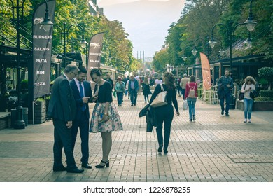 People meet, talk and look at the mobile phone. People walk on Vitosha boulevard in Sofia - The Capital of Bulgaria 10/2018