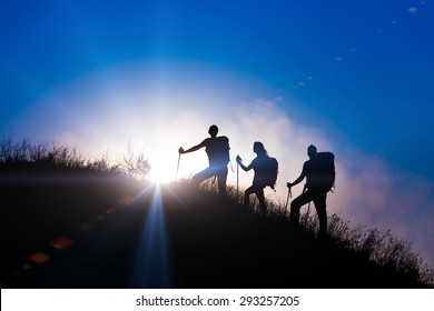 People meeting sunrise team building session. Group of people silhouettes walking toward mountain summit with backpacks hiking trekking gear meeting uprising sun sunbeams and blue sky of background