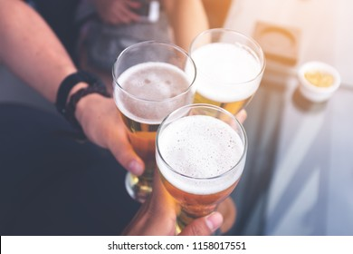 people, men, leisure, friendship and celebration concept - The group of people  drinking beer and clinking glasses on rooftop bar for celebration