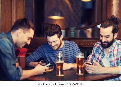 people, men, leisure, friendship and technology concept - happy male friends with smartphones drinking beer at bar or pub