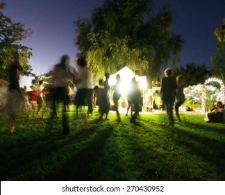 people mingling at a free concert by local musicians long exposure at night