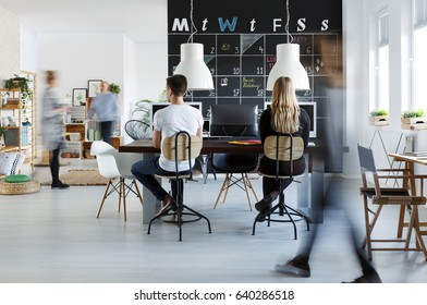 People in modern coworking space with blackboard calendar