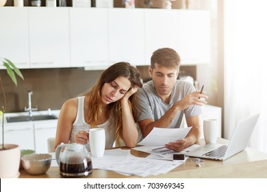 People, money and finances concept. Young tired Caucasian woman leaning at her hand and drinking morning coffee while sitting near her husband at kitchen table, working with documents and laptop