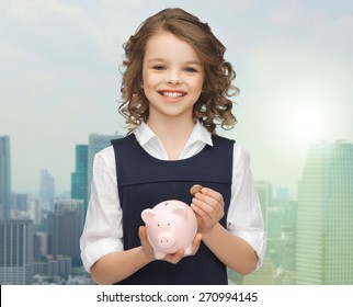 people, money, finances and savings concept - happy girl holding piggy bank and coin over city background