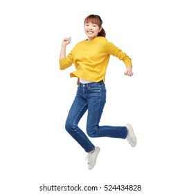 people, motion and action concept - happy asian young woman jumping over white