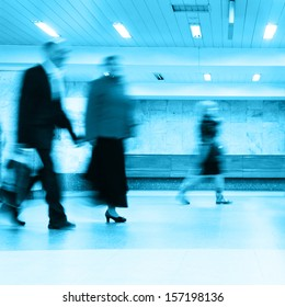 People in motion blur walking in subway station.