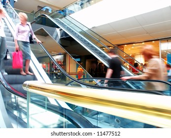 People in motion in escalators at the mall, with a golden banister at the foreground.