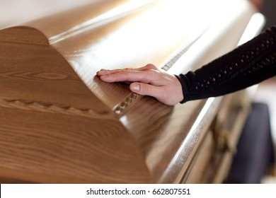 people and mourning concept - woman hand on coffin lid at funeral in church