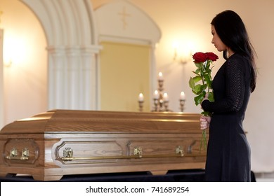 people and mourning concept - woman with red roses and coffin at funeral in church