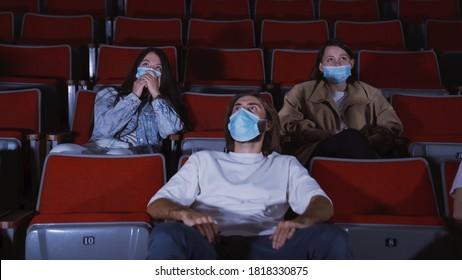 Les gens dans le cinéma regardent un film d'horreur. Médias. Je regarde des films sur des masques médicaux pendant la pandémie de coronavirus. Les gens en masques regardent des films d'horreur