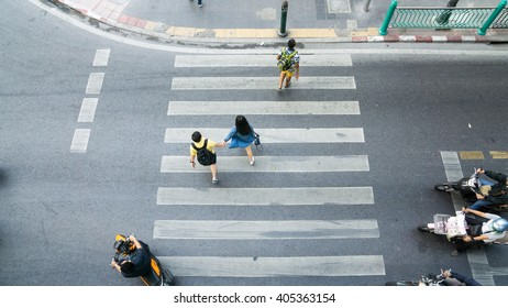 People are moving across the crosswalk on the city road (on top view)