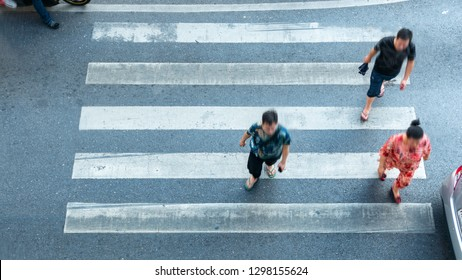 people are moving across the pedestrian crosswalk in the city road (on top view)
